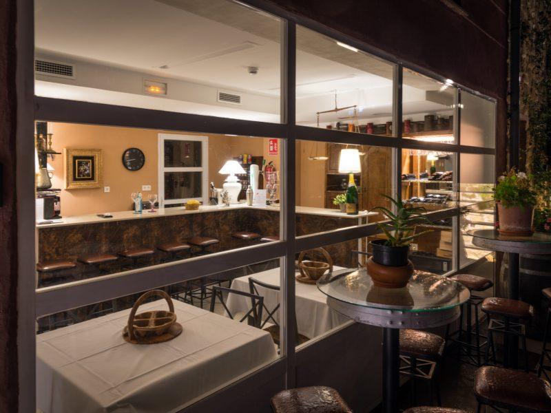 ventanales con vistas hacia el bar y sus mesas
